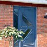 Billede af indgangsdør i blå med fyldninger og glas