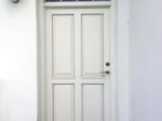 Indadgående hvid facadedør med fyldninger og glas