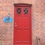 Ny indgangsdør i rød med fyldninger og glas i flot design