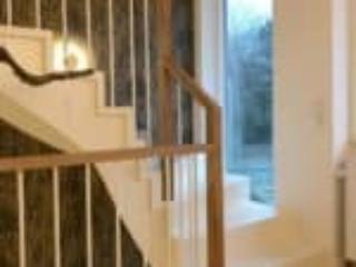 Hvid halvsvingstrappe over kældertrappe med Egetræshåndliste