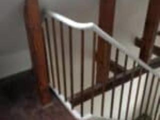 Billede af trappens mahognibalustre som matcher bjælker i entre