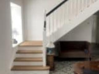Indendørs trætrappe som kvartsvingstrappe og sort håndlister
