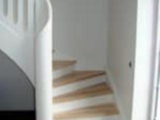 Hvid trappe som er buet med håndliste gående helt til gulv