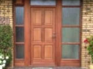 Mahogni hoveddør sammen med flere vinduespartier i mahogni