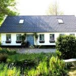 Blå vinduer og facadedør i hvidt hus med flotte naturomgivelser