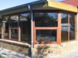 Flot designet udestue med vinduer i mahogni