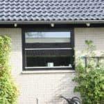 Sort topstyret vindue til hvide mursten