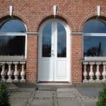 Buet facadedør med fyldninger og klar glas som dobbeltdør