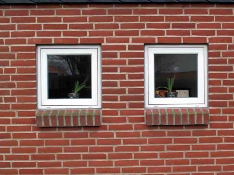 Små hvide vinduer i rød mursten og med sålbænk.